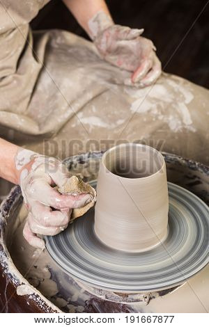 pottery, workshop, ceramics art concept - man works with potter's wheel and raw fireclay, yong male sculpt new utensils with hands, tool, fingers and water, top view, vertical