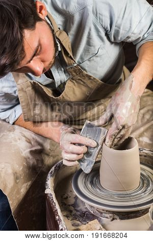 pottery, workshop, ceramics art concept - yong male sculpt some new utensils with hands, tool, fingers and water, man works with potter's wheel and raw fireclay, Mexican, Hispanic, Latino