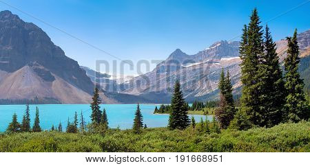 Beautiful Landscape With Azure Blue Mountain Lake And Famous Rocky Mountains In The Background In Ba