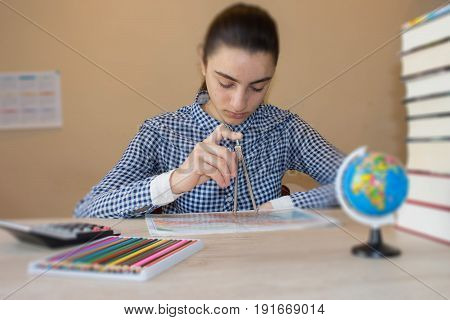 Young Girl is working with atlas at the wood table. Thoughts education creativity concept