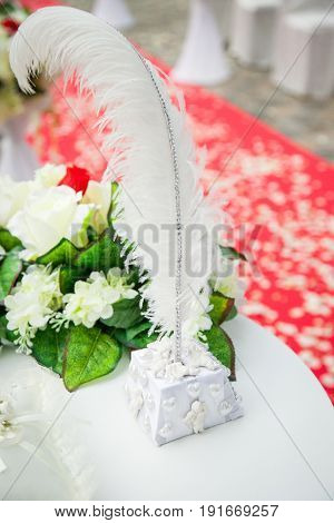 beautiful, gorgeous wedding decoration in red and white colors, feather pen, decor