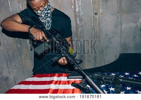 Black sniper aims at the rifle. Mercenary man with weapon in hand on dark gray background. Outlaw, ghetto, patriotic war, armed attack concept