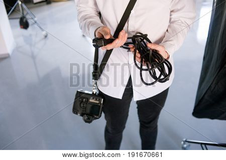Young professional photographer work in studio. Man is setting photographing equipment in studio getting ready for a photo shoot