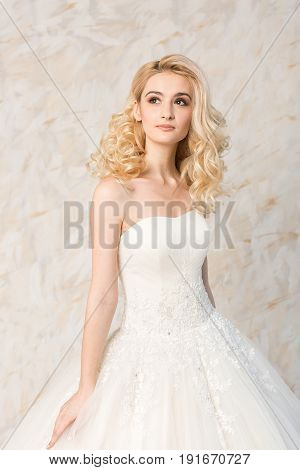 fashionable white gown, beautiful blonde model, bride hairstyle and makeup concept - young dreaming girl in wedding festive dress, standing indoors on light background, romantic slender woman posing