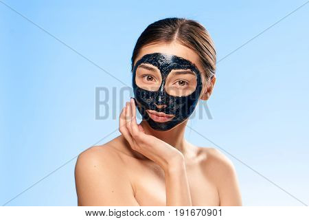 Woman in a cosmetic mask on a blue backgroun.