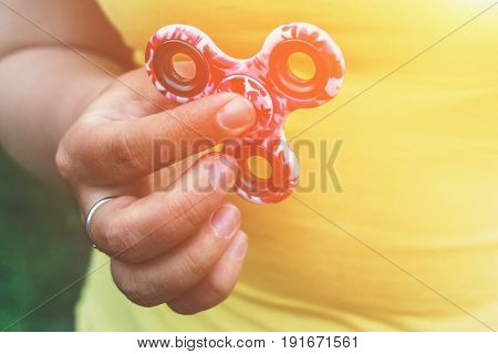 Fidget Spinner toy in girl hand, stress relieving toy, light effect