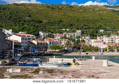 Petrovac, Montenegro - OCTOBER 13, 2016: Fishing boats on water of Petrovac harbor in Montenegro.Sunset light in Petrovac - touristic town on Adriatic riviera.
