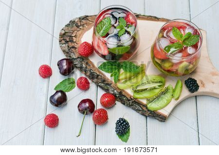 Glasses fruit water with various ingredients presented on a tree disk