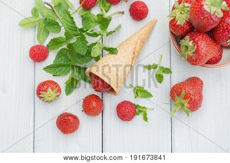 Bowl and cones filled with strawberries on a wooden table