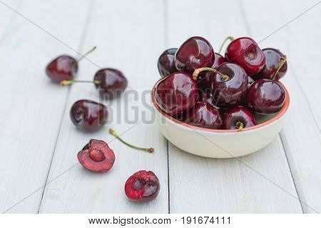 Bowl filled with cherries on a wooden table