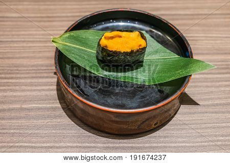 Uni Sushi Japanese Food In Black Plate On Wooden Table