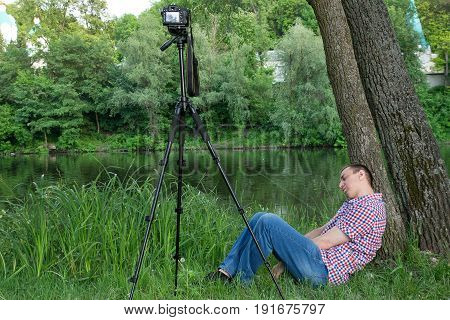 The Photographer Is Asleep While Shooting Against The Background Of The River