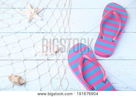 Pair Of Flip Flops With Fishnet And Starfish On Wooden Table