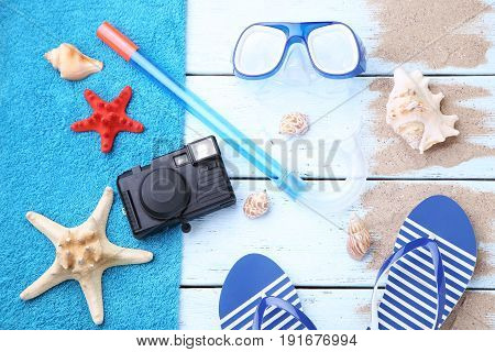 Diving snorkel and mask with starfish flip flops and camera on wooden table