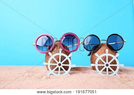 Coconuts With Sunglasses And Ship Wheels On Beach Sand