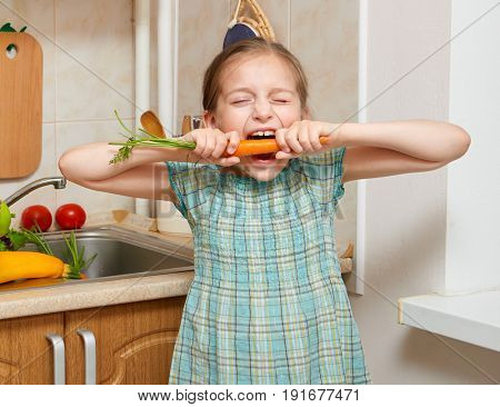 child girl eat carrot, vegetables and fresh fruits in kitchen interior, healthy food concept