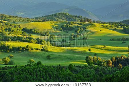 Spring forest and meadows landscape in Slovakia. Morning scenery near village Poniky. Fresh trees and pastures. Sunlit country.