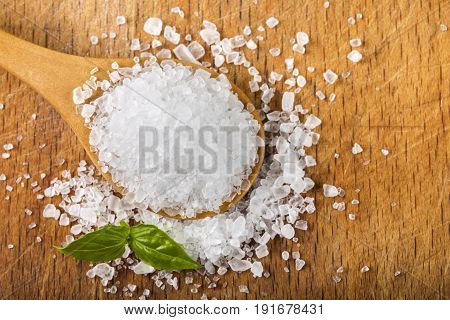 Sea salt in wooden spoon with basil leaf over wood background