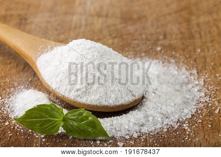Salt. Coarse grained sea salt on wooden background