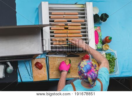 Top view of Cooking barbecue. Man with healthy vegan street food, sausages, Hot Dogs made with soy protein wiener on vegan hot dog bun, vegetables, selective focus. Summer bbq grill background concept
