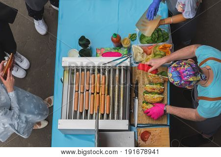 High angle view of cooking barbecue. Man with healthy vegan street food, sausages, made with soy protein wiener on vegan hot dog bun, vegetables. Summer healthy vegan bbq grill concept