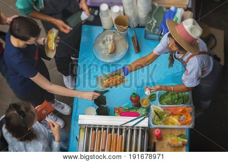 High angle view of barbecue. Sale and service with Vegan Hot Dog made with soy protein wiener on vegan hot dog bun, vegetables, selective focus. Top view. Healthy vegan street food concept