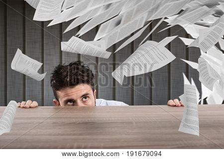 Businessman afraid under the desk under flying sheet. concept of overwork