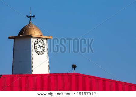 Vibrant seaside pier clock tower with weathervane. Britannia pier Great Yarmouth Norfolk UK. With blue sky background and copy space. poster