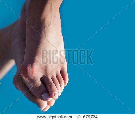 bone on foot toe with pedicure reflecting in mirror on blue background copy space medicine and health relax and tiredness age and evolution