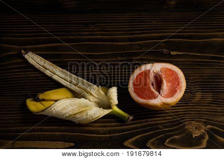 banana yellow peel and red grapefruit on wooden background fruit love and summer vitamin and dieting healthy food penis and vagina
