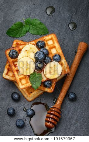 Traditional Belgian Waffles With Blueberries, Banana And Honey On A Black Slate Plate. Gourmet Break