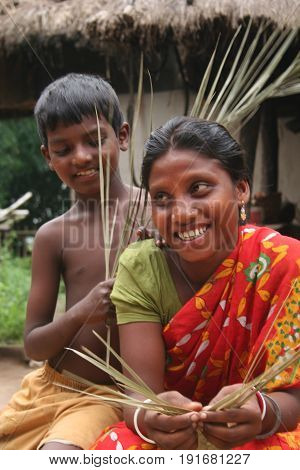 DURGAPUR, SEPTEMBER 27, 2008: A tribal woman is making handicraft from leafs with her child on September 27, 2008 in tribal village near Durgapur, India.
