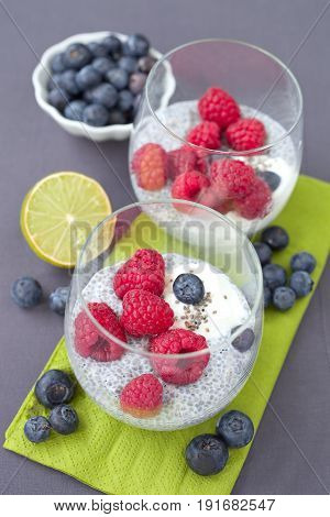 Healthy chia seed pudding with raspberry and blueberry in a glass jar.
