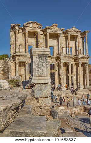 EFES, TURKEY - OCTOBER 1: Roman inscription, on a stone in the front of Library of Celsus with a goup of tourist on October 1, 2011 in Efes, Turkey.