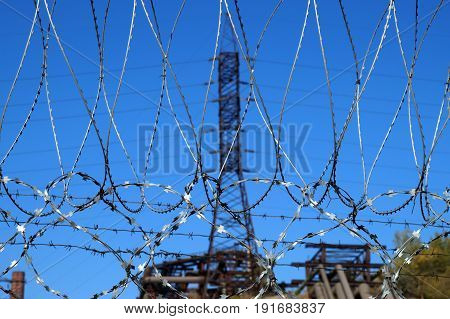 Barbed wire against a mast of power lines in an industrial zone