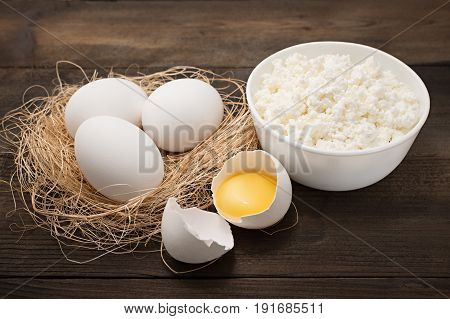 Dairy products on wooden background. Cottage cheese, egg and egg yolk. Top view with copy