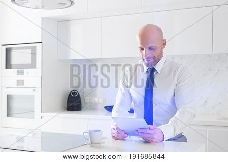 Mid adult businessman using tablet PC in kitchen