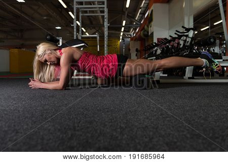 Young Sporty Fit Woman Stretches With Roller