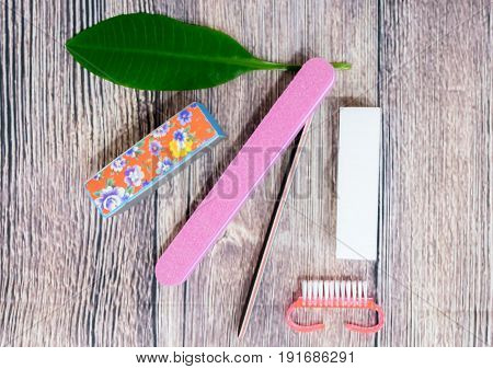 set with cosmetic nail file hard polishing brush for manicure and care on wooden background concept care style