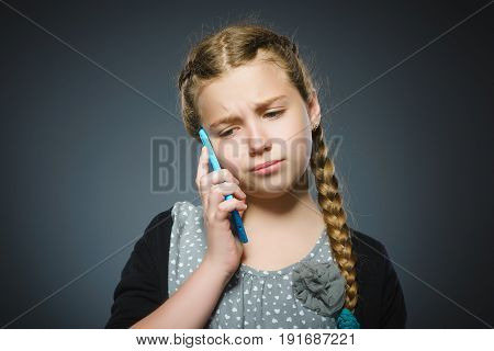 Cute little girl speaking on the cell phone. isolated on gray.