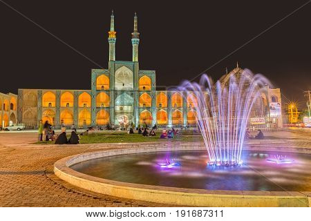 YAZD, IRAN - MAY 5, 2015: People socializing by the fountain and Amir Chakhmaq Complex in old city. Long exposition.