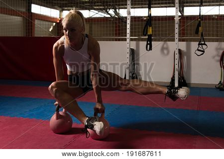 Healthy Woman Stretching With Kettle Bell