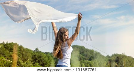 Beautiful woman holding a white scarf that flies in the wind