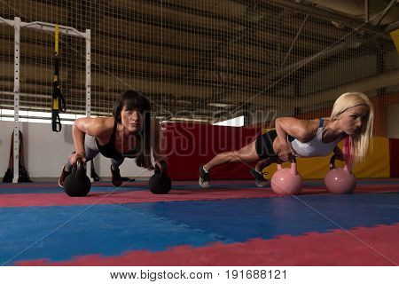 Fitness Couple Exercising With Kettle-bell