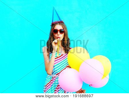 Pretty Young Woman In A Birthday Cap Blowing A Whistle Holds An
