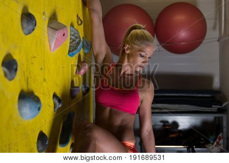 Struggling To Reach Handhold On Climbing Wall