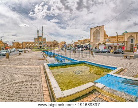 YAZD, IRAN - MAY 5, 2015: People socializing by the fountain and Amir Chakhmaq Complex in old city.