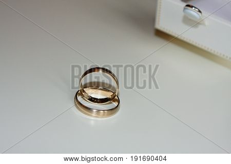 golden wedding rings with white box .
