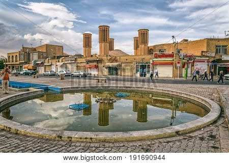 YAZD, IRAN - MAY 5, 2015: Windcatcher towers is a traditional Persian architectural element to create natural ventilation in buildings, view from the fountain on Amir Chakhmaq square in old city.