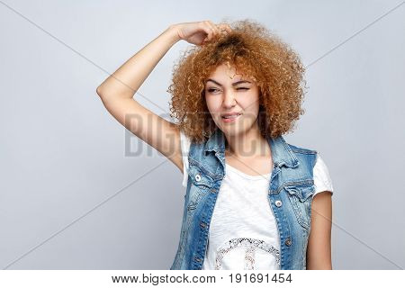 Portrait of beautiful thoughtful curly mixed race girl in casual style is thinking. studio shot on light gray background.